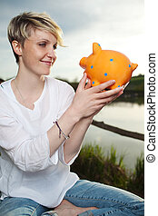 Young Woman Looking At Piggy Bank Outdoors