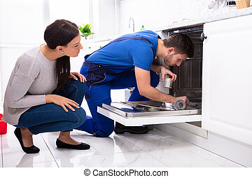 Woman Looking At Repairman Repairing Dishwasher In Kitchen