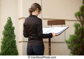 Young woman looking at restaurant menu on the street