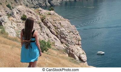 woman looking at sailing motorboat