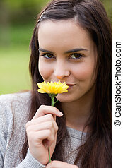 Young woman looking at the camera while standing upright and smelling a flower