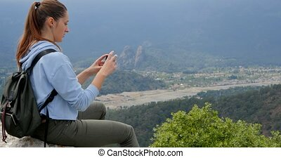 Young woman looking at the city below from the high point of...