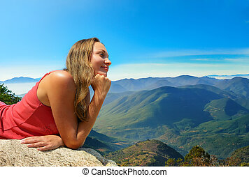 Young woman looking at the mountains on the edge of a cliff
