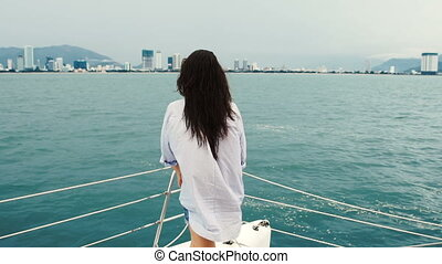 Young woman looking at the ocean and rise hands while enjoying a cruise on yacht