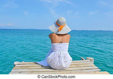 Young woman looking at the sea from a dock