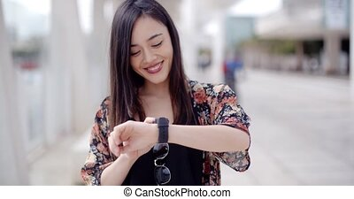 Young woman looking at the time with a smile