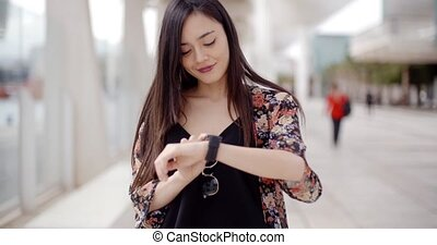 Young woman looking at the time on her wristwatch with a smile as she stands outdoors in an urban environment close up upper body