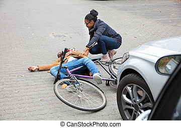 Woman Looking At Unconscious Male Cyclist Lying On Street
