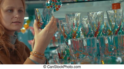 Young woman looking at Venetian glass in the store
