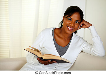 Young woman looking at you while holding a book