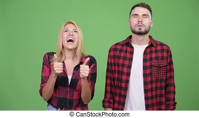 Young woman looking excited with young man having headache...