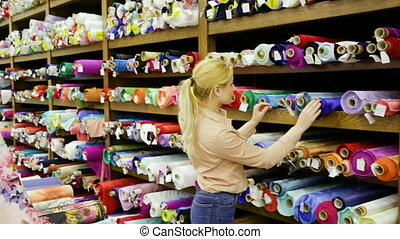 Young woman looking for interesting cloth in textile shop