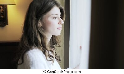 Young woman looking in a window in the morning, close up