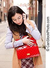young woman looking in her bag while on the phone