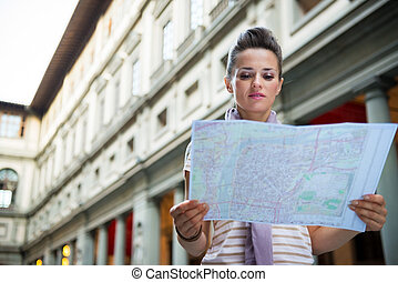Young woman looking in map near uffizi gallery in florence, italy