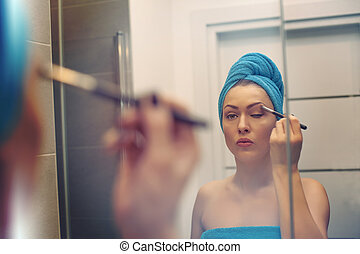 Young woman looking in the mirror and putting make-up