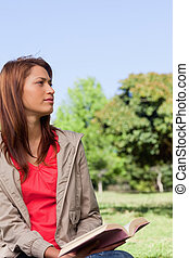 Young woman looking into the distance while sitting down...