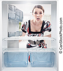 Young woman looking on empty shelf in fridge.