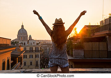 Young woman looking on rooftops of rome on sunset and...