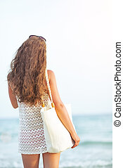 Young woman looking on sea. rear view