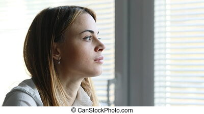 young woman looking out of her office window