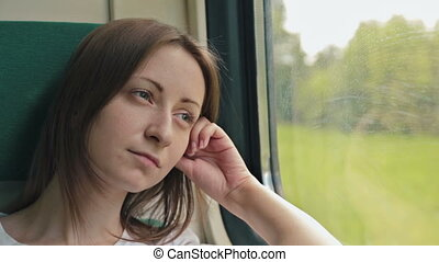 young woman looking out the window of a train
