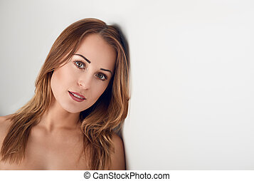 Young woman looking over her bare shoulder