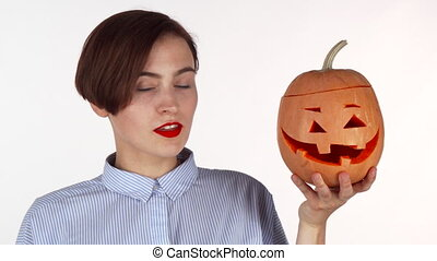 Young woman looking shocked, posing with halloween carved pumpkin