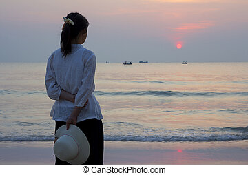 Young woman looking sunrise on the beach