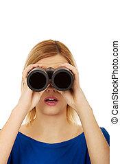 Young woman looking through a binocular