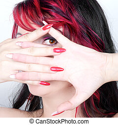Young woman looking through a hole in her fingers