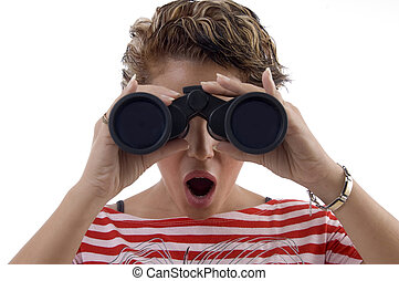 young woman looking through binocular against white...