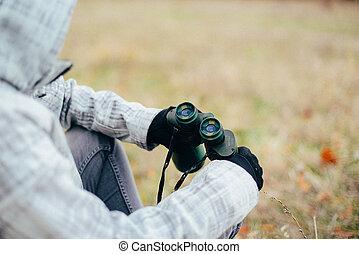 Young woman looking through binoculars on a autumn nature. Binocular, traveler, hiking.  young caucasian female hiker holding in his hand binoculars. Horizontal shape, front view,