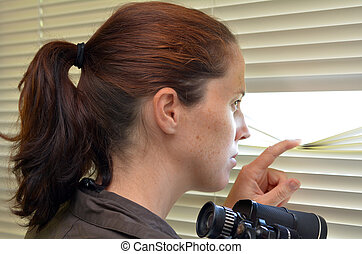 Young woman looking through blinds - Young woman (age 25-30...