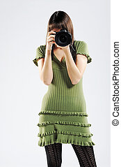 young woman looking through slr camera