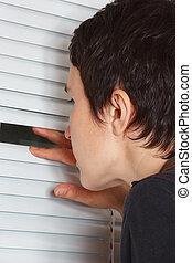 Young woman looking through the blinds of a light room