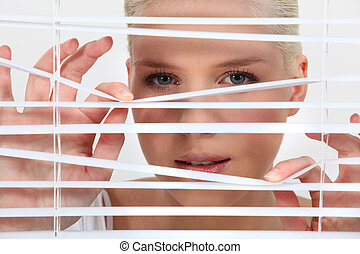 young woman looking through the blinds