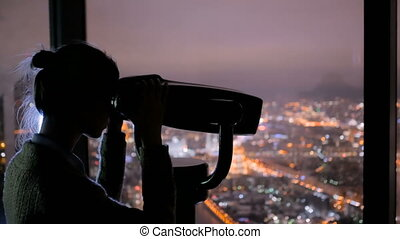 Young woman looking through tourist telescope and exploring...