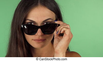 Young woman looking to the camera over her sunglasses -...
