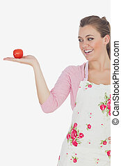 Young woman looking tomato