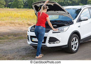 Young woman looking under the hood of broken car at countryside road