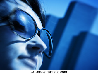 Young woman looking up at the business skyscrapers, conceptual blue tint