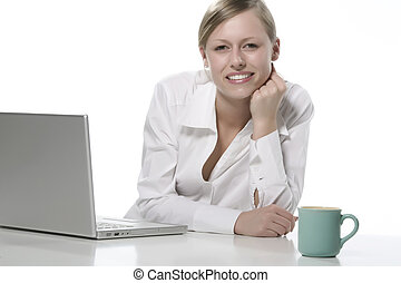Young woman looks at her laptop computer and drinks her coffee.