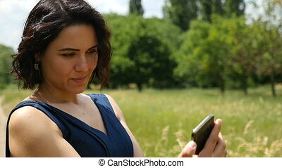 Young woman looks at her smartphone and smiles romantically on a lawn in slo-mo