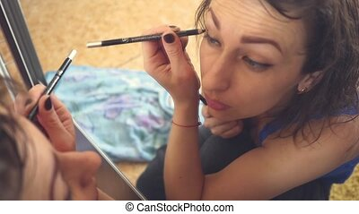 Young woman looks at herself in the mirror and does makeup