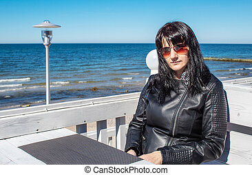 young woman looks at the sea sitting in the outdoor cafe