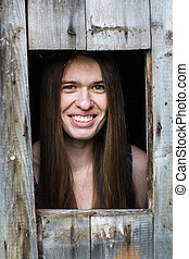 Young woman looks from the little window of a wooden barn.