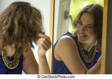 woman looks in the mirror.