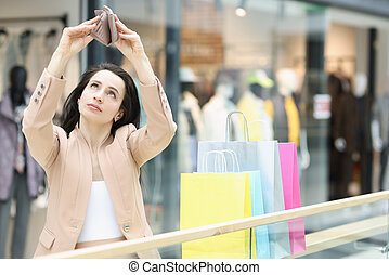 Young woman looks into empty wallet in mall