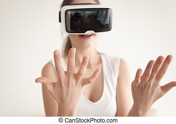 Young woman looks on own hands through VR glasses
